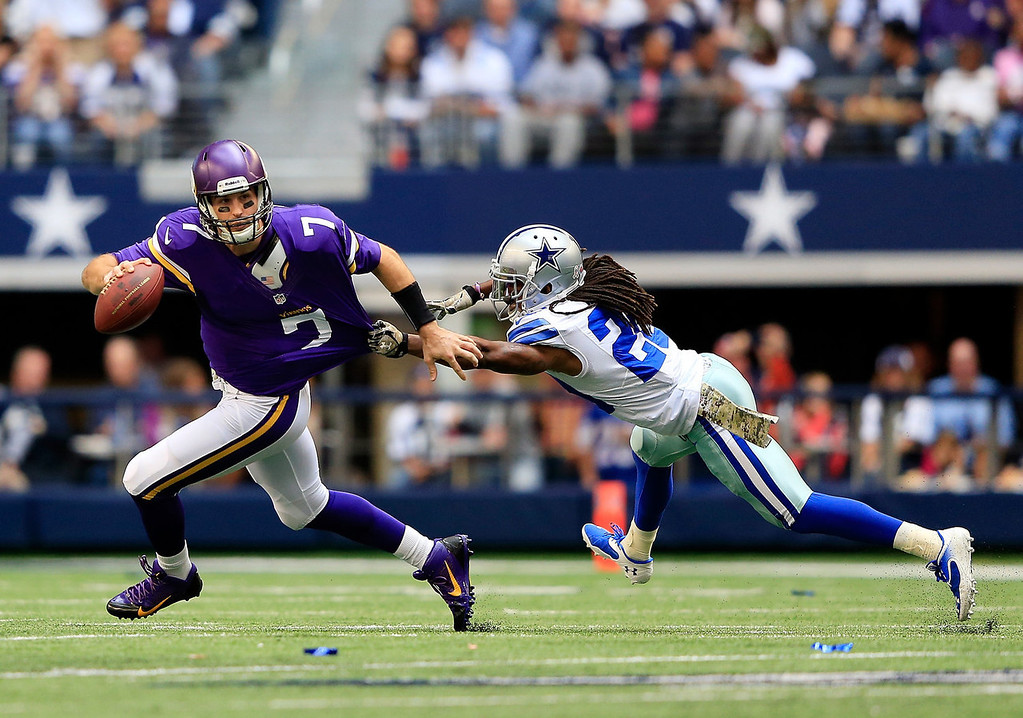 . Quarterback Christian Ponder #7 of the Minnesota Vikings is chased by cornerback B.W. Webb #20 of the Dallas Cowboys during the game at Cowboys Stadium on November 3, 2013 in Arlington, Texas.  (Photo by Jamie Squire/Getty Images)
