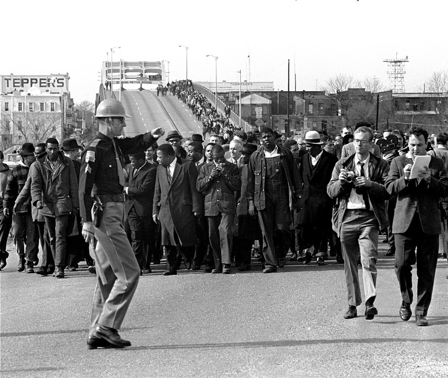 . Demonstrators, including Dr. Martin Luther King, Jr., stream over an Alabama River bridge at the city limits of Selma, Ala., in this March 10, 1965 file photo, during a voter rights march. (AP Photo, File)