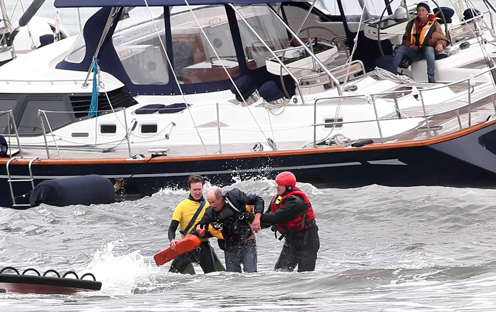 . A man is rescued from the 82-foot-long sailboat, the Darling, stuck in the surf off Linda Mar Beach in Pacifica, Calif., Monday morning March 4, 2013. The boat had been reported stolen from a Sausalito marina earlier. The man, and two others on aboard were all safely rescued and then promptly arrested. (Karl Mondon/Staff)