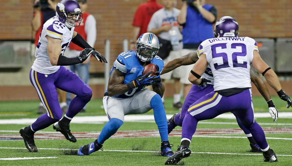 . Lions wide receiver Calvin Johnson, center, makes a reception between the defense of Vikings free safety Harrison Smith, left, and outside linebacker Chad Greenway during the second quarter.  (AP Photo/Paul Sancya)