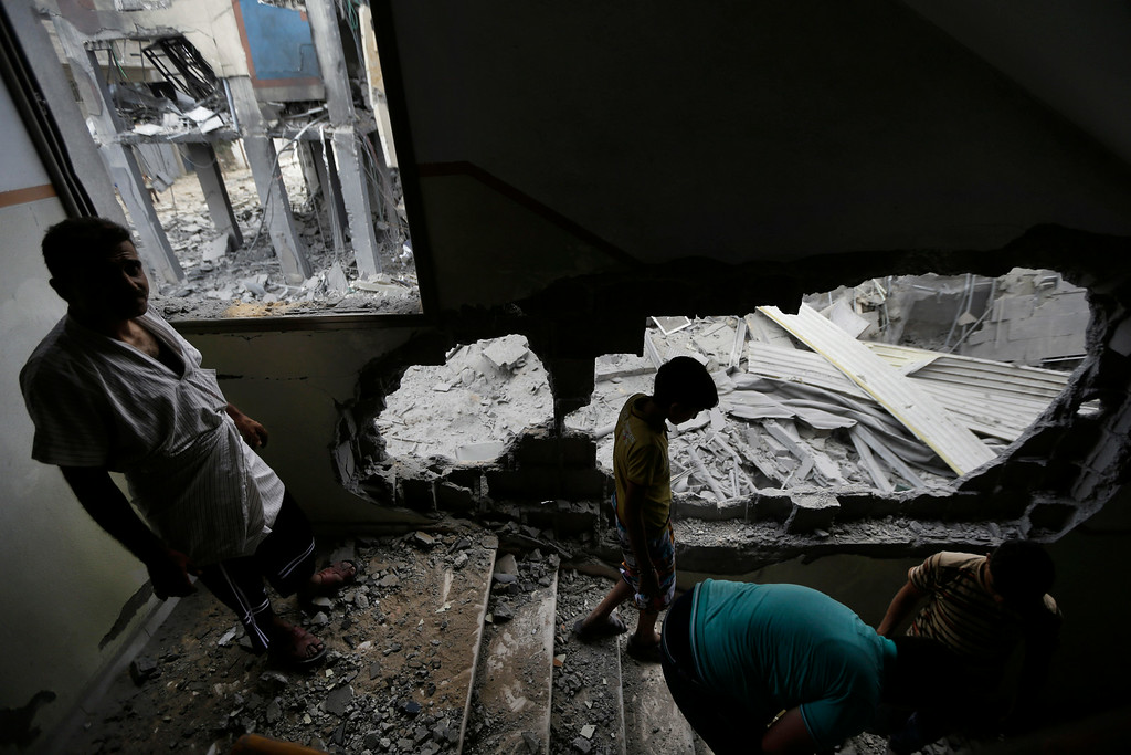 . Palestinians clear the debris as they inspect the damage of the offices of the Hamas movement\'s Al-Aqsa satellite TV station, in Gaza City, northern Gaza Strip, destroyed by an Israeli strike, Tuesday, July 29, 2014. (AP Photo/Lefteris Pitarakis)