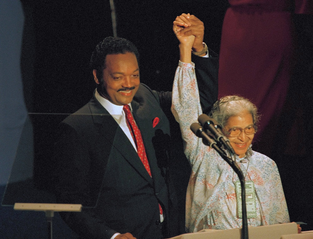 Description of . Jesse Jackson raises the arm of Rosa Parks as he honored the heroine of the Montgomery bus boycott  of 1955, during his appearance before the Democratic National Convention in Atlanta, July 19, 1988. Jackson saluted Democratic nominee-to-be Michael Dukakis as a rival who always resisted the temptation to stoop to demagoguery. (AP Photo)