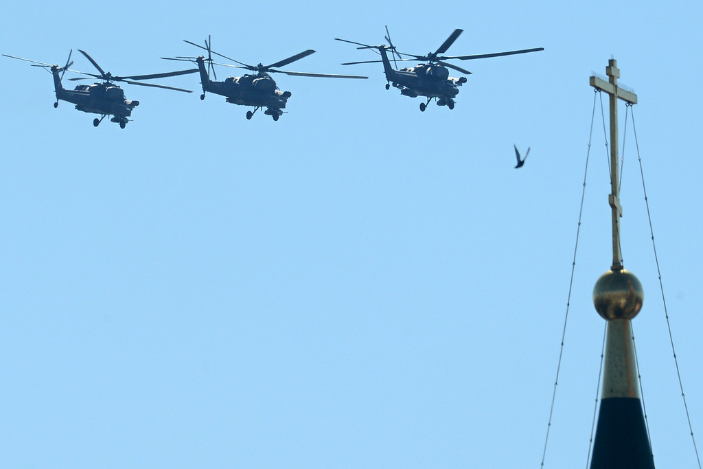 . Russian Mil Mi-28 helicopter gunships fly above the Kremlin\'s cathedrals in Moscow, on May  9, 2014, during a Victory Day parade.  AFP PHOTO / KIRILL KUDRYAVTSEV/AFP/Getty Images