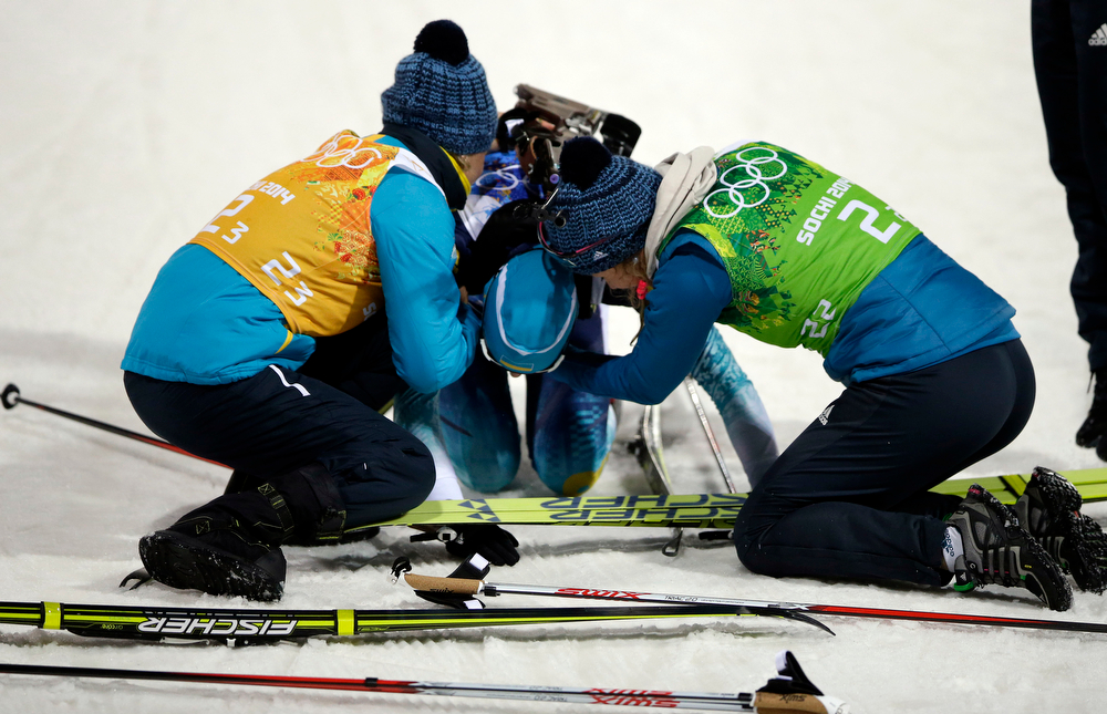 . Ukraine\'s Olena Pidhrushna, center, celebrates with Valj Semerenko, left, and  Juliya Dzhyma after winning the gold medal in the women\'s biathlon 4x6k relay at the 2014 Winter Olympics, Friday, Feb. 21, 2014, in Krasnaya Polyana, Russia. (AP Photo/Lee Jin-man)