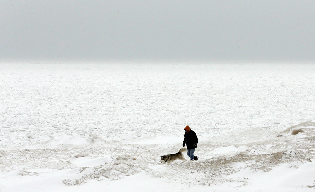 Description of . A man walks with his dog next to the snow-covered Lake Michigan in Chicago on Friday, Feb. 22, 2013. Gusty winds and iced-over roadways made for treacherous Midwest travel Friday as a major winter storm headed east over the Great Lakes. (AP Photo/Nam Y. Huh)