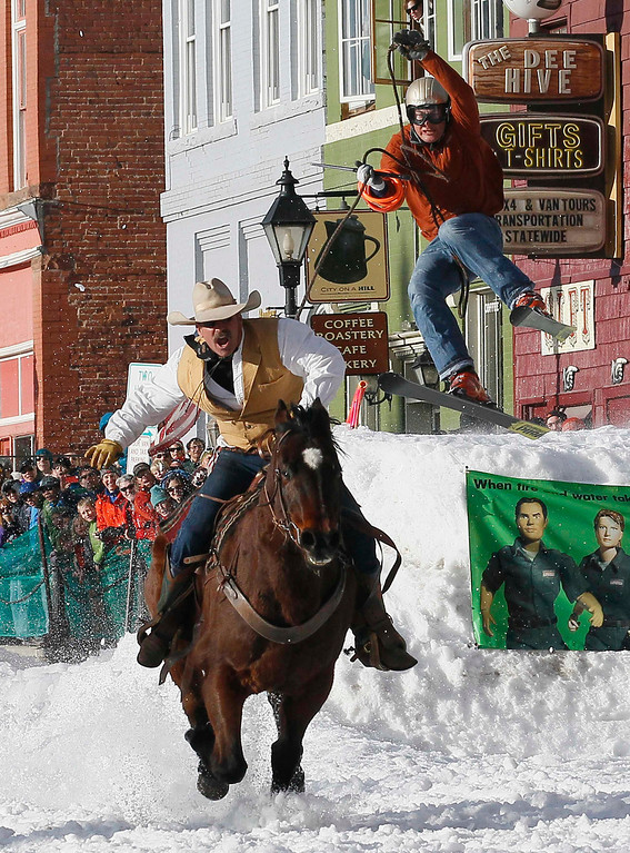 . A horseman pulls a skier down the snow-covered main street during the annual skijoring race in downtown Leadville, Colorado March 2, 2013. This was the 62nd year for the competition in Leadville.  REUTERS/Rick Wilking