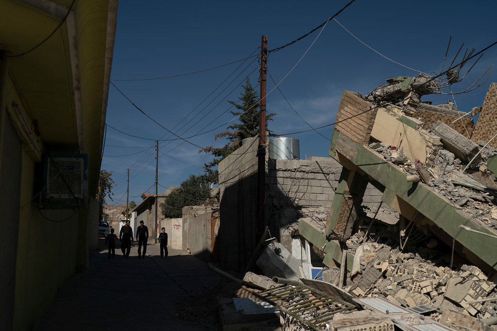 . People walk next to a destroyed house after an earthquake at the city of Darbandikhan, northern Iraq, Monday, Nov. 13, 2017. A powerful 7.3 magnitude earthquake near the Iraq-Iran border has killed over 350 people across both countries, sent residents fleeing their homes into the night and was felt as far away as the Mediterranean coast. (AP Photo/Felipe Dana)