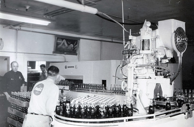 Harry Meyer (far left) in the Chadron Coca-Cola Bottling plant. (Undated)