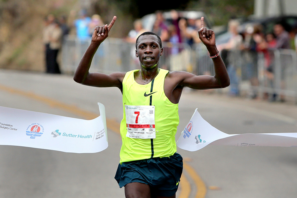 . Simon Ndirangu of Kenya crosses the finish line to take first place in the 42nd annual Wharf to Wharf road race in Capitola on Sunday morning. (Kevin Johnson -- Santa Cruz Sentinel)