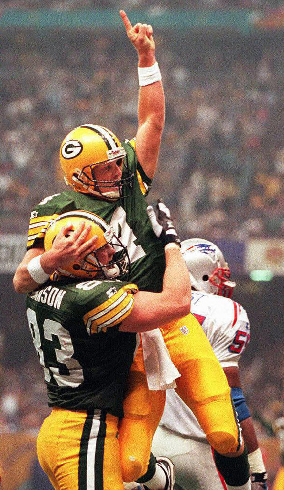 . Green Bay Packers quarterback Brett Favre (C) is hoisted in the air by teammate Jeff Thomason (L) after Favre ran for a touchdown to give Green Bay a 27-14 lead over the New England Patriots in the second quarter of Super Bowl XXXI at the Louisiana Superdome in New Orleans, Louisiana 26 January. Patriots linebacker Todd Collins is rear right. DON EMMERT/AFP/Getty Images