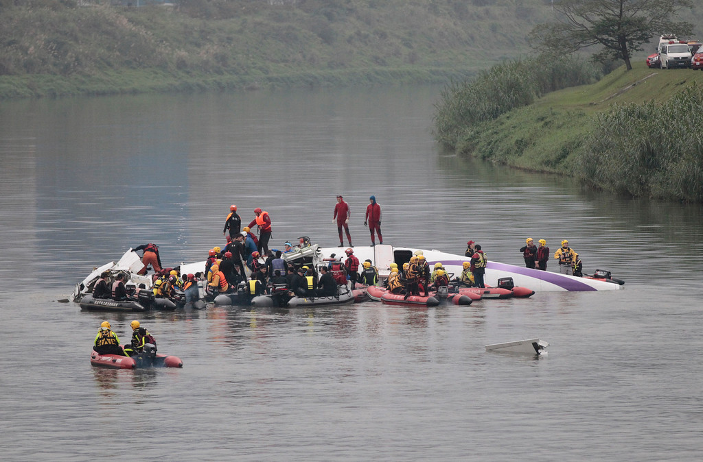 . Emergency personnel try to extract passengers from a commercial plane after it crashed in Taipei, Taiwan Wednesday, Feb. 4, 2015. The Taiwanese commercial flight with 58 people aboard clipped a bridge shortly after takeoff and crashed into a river in the island\'s capital on Wednesday morning. (AP Photo/Wally Santana)
