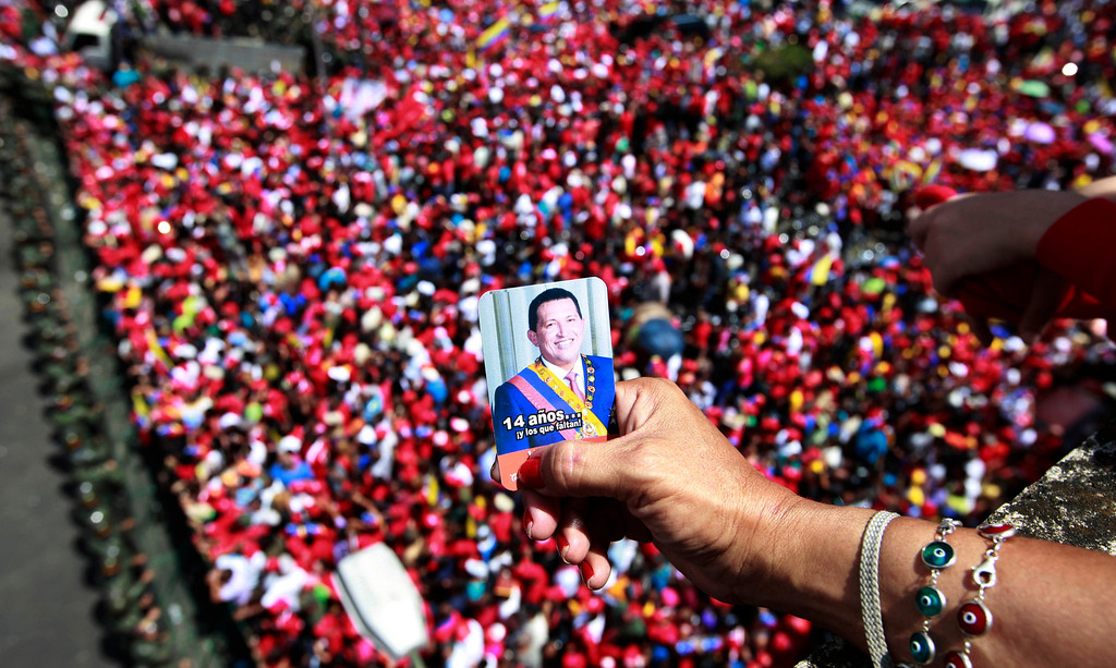 . A supporter of Venezuela\'s late President Hugo Chavez holds a picture of him above a crowd waiting for Chavez\'s coffin to be taken from the hospital where he died on Tuesday, to a military academy where it will remain until his funeral in Caracas, Venezuela, Wednesday, March 6, 2013.  (AP Photo/Ricardo Mazalan)
