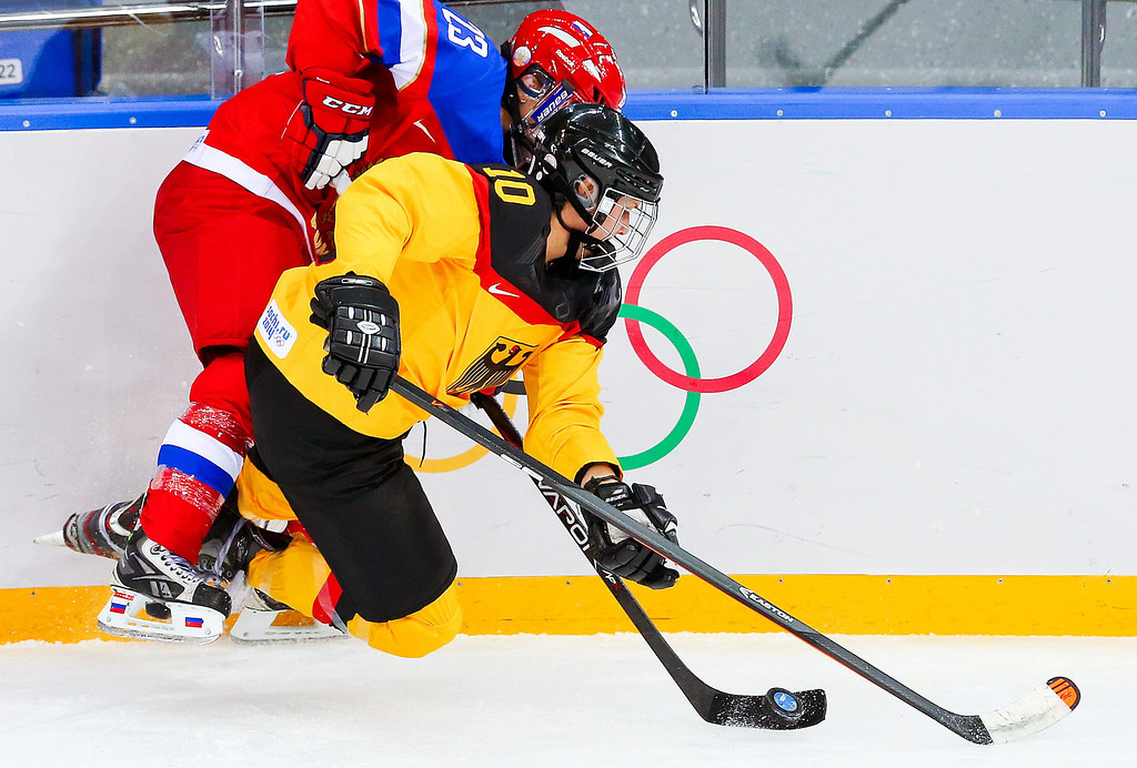 . Anja Weisser (R) of Germany fights for the puck with Tatyana Burina (L) of Russia  in the first period during the women\'s match between Russia and Germany at the Shayba Arena in the Ice Hockey tournament at the Sochi 2014 Olympic Games, Sochi, Russia, 09 February 2014.  EPA/SRDJAN SUKI