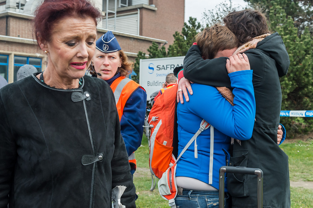 . People react outside Brussels airport after explosions rocked the facility in Brussels, Belgium Tuesday March 22, 2016.   Explosions rocked the Brussels airport and the subway system Tuesday, just days after the main suspect in the November Paris attacks was arrested in the city, police said. (AP Photo/Geert Vanden Wijngaert)