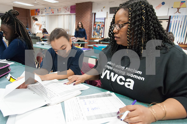 01/11/18 Wesley Bunnell | Staff 45 students from Slade Middle School participate in an American Savings Foundation funded program through the YWCA for youth development opportunities. Activities involve homework, social programs and team building activities. Katerina Evans, L, sits with YWCA worker Genese Simmons as she checks off her notebook for good behavior and attendance to quality for a field trip to Flight Trampoline Park.