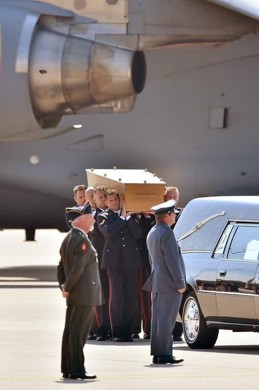 . Dutch military men carry a coffin containing the body of a victim of downed Malaysia Airlines flight MH17, during a ceremony at Eindhoven Airbase on July 23, 2014, after a Hercules transport plane carrying the coffins landed from Ukraine. The first bodies from flight MH17 arrived in the Netherlands on July 23 almost a week after it was shot down over Ukraine, with grieving relatives and the king and queen of The Netherlands solemnly receiving the as yet unidentified victims. AFP PHOTO / JOHN  THYS/AFP/Getty Images