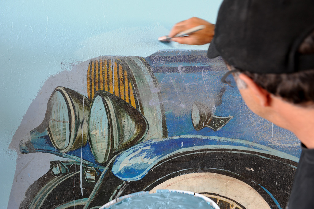 """. Joe Nicoletti paints during the restoration of the mural \""""Panorama: G.M. Recollections from the Past,\"""" on Van Nuys Boulevard in Panorama City, Thursday, June 20, 2013. The original mural was painted by Alfredo Diaz Flores in 1998 and pays homage to the General Motors plant that used to be near the mural site. (Michael Owen Baker/Staff Photographer)"""