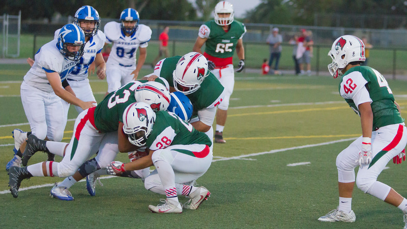 Lindsay defenders Cody Melher (63), Ethan Duran (28) and Pedro Avila (71) gang tackle an Avenal ball carrier in Lindsay's 15-8 victory.