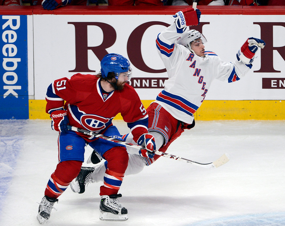 . New York Rangers left wing Daniel Carcillo is checked by Montreal Canadiens center David Desharnais (51) during the first period in Game 2 of the NHL hockey Eastern Conference final Stanley Cup playoff game Monday, May 19, 2014, in Montreal. (AP Photo/The Canadian Press, Ryan Remiorz)