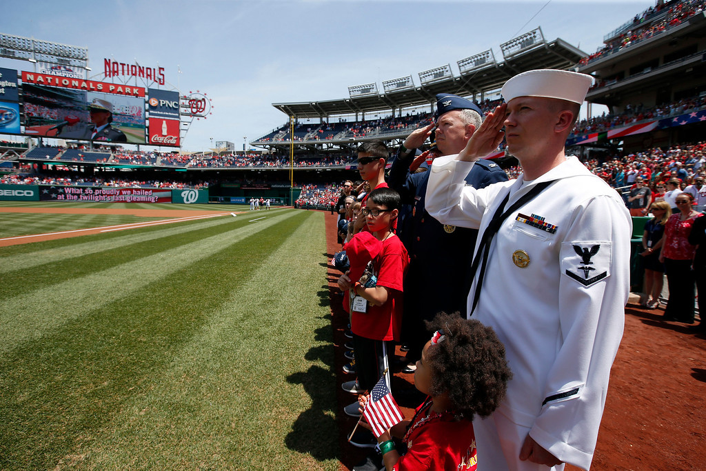 . U.S. Navy Hospitalman Third Class Johnathan Loper, right, and others salute during the National Anthem before a baseball game between the Washington Nationals and the Miami Marlins at Nationals Park, on Memorial Day, Monday, May 26, 2014, in Washington. (AP Photo/Alex Brandon)
