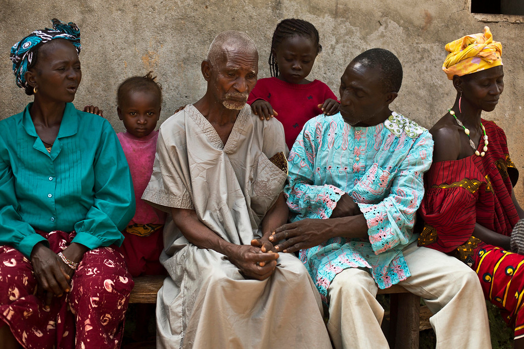 . In this photo taken Thursday Nov. 20, 2014, Kissi Dembadouno, center, is comforted by relatives  outside his home in the Guinean village of Meliandou, some 400 miles (600 kms) south-east of Conakry, Guinea, believed to be Ebola\'s ground zero. Demnadouno lost his wife, daughter and two grandchildren to the deadly disease. He is Etienne Ouamouno\'s father in law. The first reported case of Ebola is Etienne\'s son, Emile, who passed away  late Dec. 2013. (AP Photo/Jerome Delay)