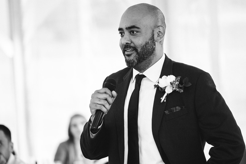 The groomsman smiling, delivering a speech.