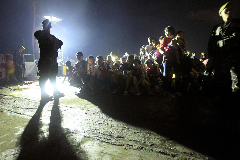 . Soldiers watch over Typhoon Haiyan survivors as they wait for the last evacuation flight at the airport in Tacloban, central Philippines, Thursday, Nov. 14, 2013.  (AP Photo/Wally Santana)