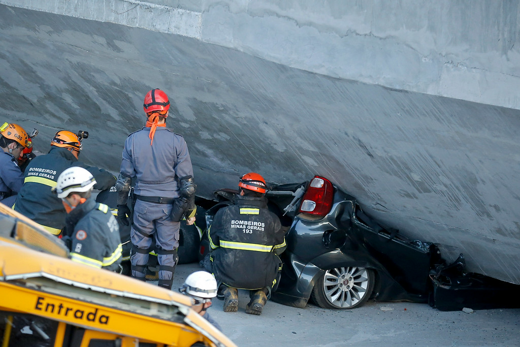 . Fire department personnel work to retrieve a car pressed underneath a collapsed bridge in Belo Horizonte, Brazil, Thursday, July 3, 2014. The overpass under construction collapsed Thursday in the Brazilian World Cup host city. The incident took place on a main avenue, the expansion of which was part of the World Cup infrastructure plan but, like most urban mobility projects related to the Cup, was not finished on time for the event. (AP Photo/Victor R. Caivano)