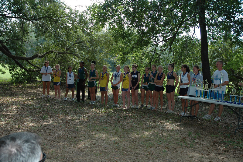 GODBY COUGAR XC CHALLENGE AWARDS: Girls' 1st-15th, right-to-left. Winner Laura Hempel's splits, as I got them from my lead bike duties: 400m/1:23, 800m/2:50, 1k/3:38, 1200m/4:28, 1M/6:14, 2k/8:04, 2.5k/10:09, 3k/12:15, 2M/13:12, 4k/16:xx, 3M/20:0x, 5k/20:43 Guy Sanders' head, lower-left; Race Director and Godby XC Coach Chris Sumner, far right, behind the trophy table.