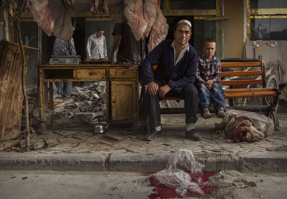 . KASHGAR, CHINA - JULY 28:  A Uyghur butcher and his son wait for customers before the Eid holiday on July 28, 2014 in old Kashgar, Xinjiang Province, China. Nearly 100 people have been killed in unrest in the restive Xinjiang Province in the last week in what authorities say is terrorism but advocacy groups claim is a result of a government crackdown to silence opposition to its policies. China\'s Muslim Uyghur ethnic group faces cultural and religious restrictions by the Chinese government. Beijing says it is investing heavily in the Xinjiang region but Uyghurs are increasingly dissatisfied with the influx of Han Chinese and uneven economic development.  (Photo by Kevin Frayer/Getty Images)