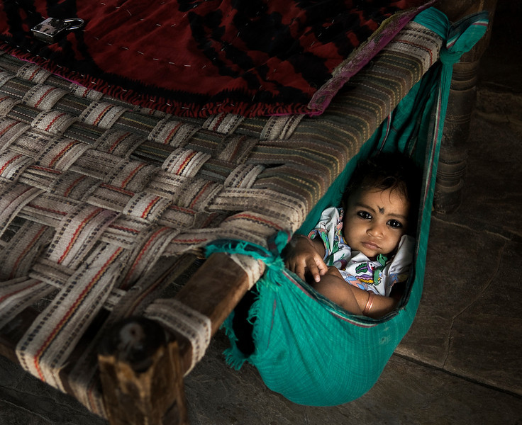 The caretaker at a local school leaves her daughter resting on a hammock whist she gets on with her duties.  Budi, Rajasthan, India, 2011.