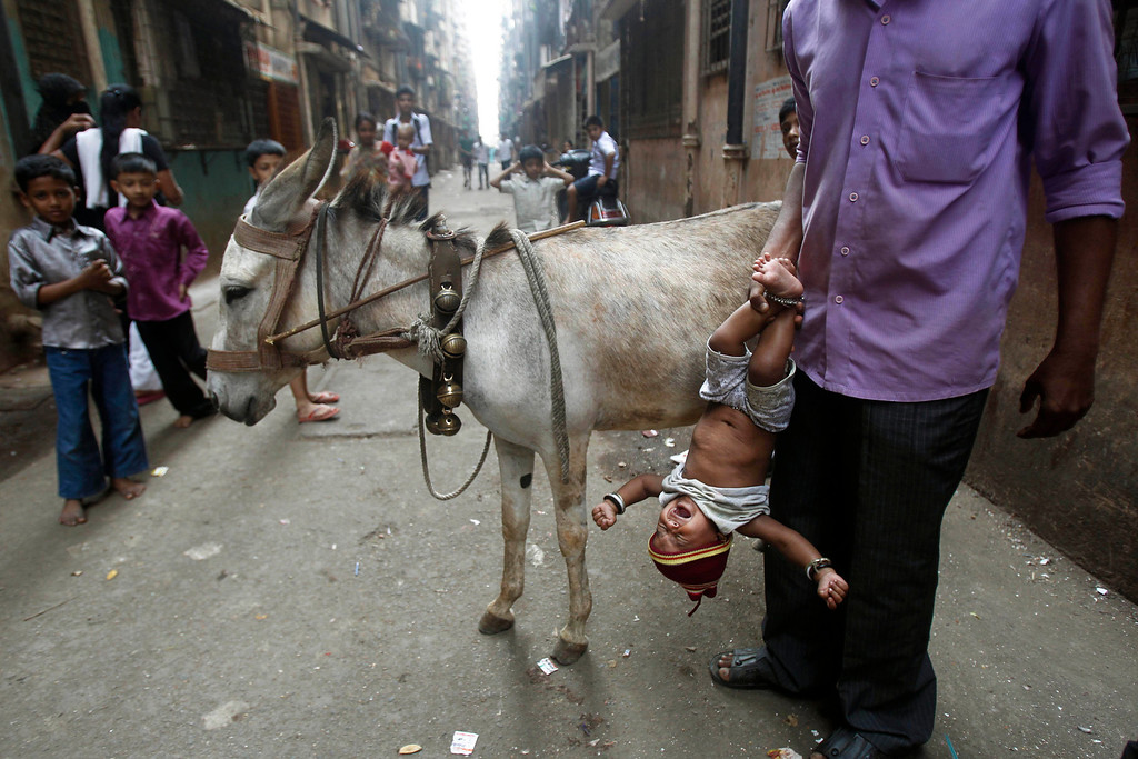 . In this Feb. 29, 2012 file photo, Santosh, who sells donkey milk, holds a baby upside down after feeding him some of the liquid, locally believed to be a cure for a persistent cough in a slum in Mumbai, India. Millions of children are growing up in squalid urban areas and denied basic services despite living close to them. UNICEF said children living in slums and shantytowns often lack water, electricity and healthcare and urged policy makers to ensure urban planning meets the needs of children. (AP Photo/Rafiq Maqbool, File)