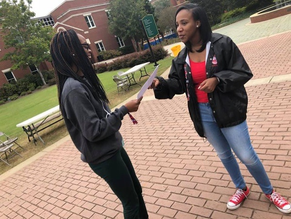 Jasia Clark passing out absentee ballot information for a political awareness event hosted by the Nu Tau Chapter of Delta Sigma Theta Sorority, Inc.