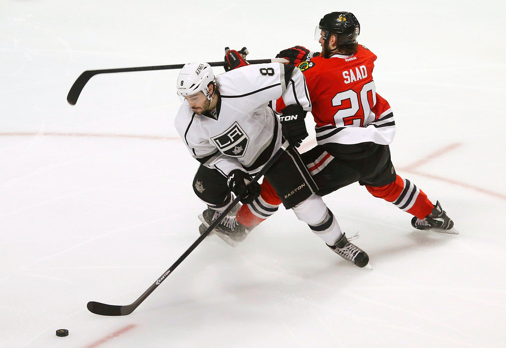 . Los Angeles Kings defenseman Drew Doughty (8) gets tangled up with Chicago Blackhawks left wing Brandon Saad (20) during the third period in Game 1 of the NHL hockey Stanley Cup Western Conference finals Saturday, June 1, 2013, in Chicago. (AP Photo/Charles Rex Arbogast)