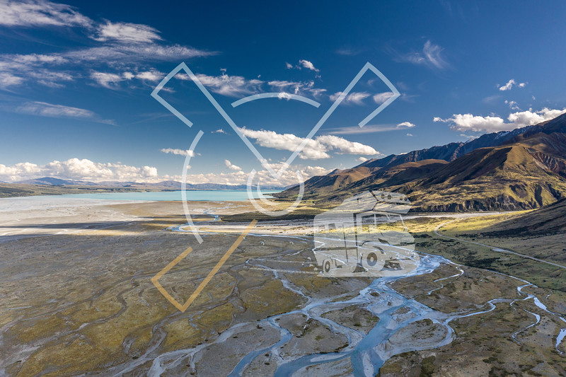 Aerial image showing the Tasman River, an alpine braided river flowing through Canterbury, in New Zealand's South Island, running into the turquoise Lake Pukaki.