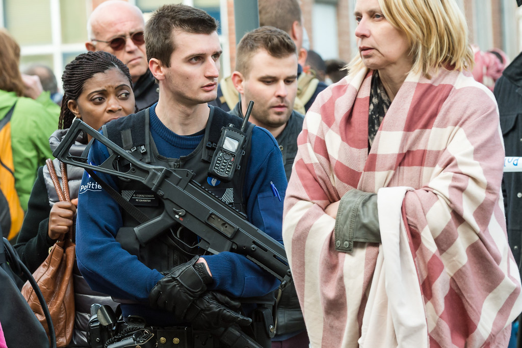 . A police officer stands guard as people are evacuated from Brussels airport, after explosions rocked the facility in Brussels, Belgium, Tuesday March 22, 2016. Authorities locked down the Belgian capital on Tuesday after explosions rocked the Brussels airport and subway system, killing  a number of people and injuring many more. Belgium raised its terror alert to its highest level, diverting arriving planes and trains and ordering people to stay where they were. Airports across Europe tightened security. (AP Photo/Geert Vanden Wijngaert)