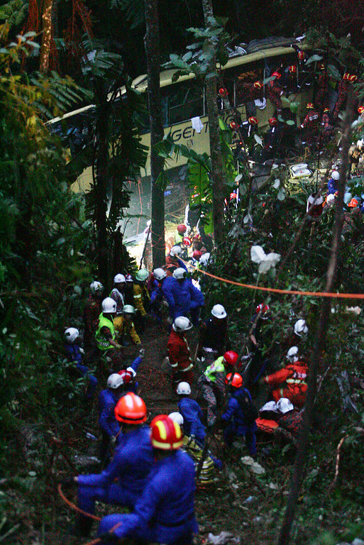 . Malaysian emergency services personnel  search for passenger after a bus carrying tourists and local residents fell into a ravine near the Genting Highlands, about an hour\'s drive from Kuala Lumpur, Malaysia, Wednesday, Aug. 21, 2013.  A passenger bus plunged into a deep ravine Wednesday while traveling downhill near a Malaysian highland resort, killing 33 people, an official said. (AP Photo)
