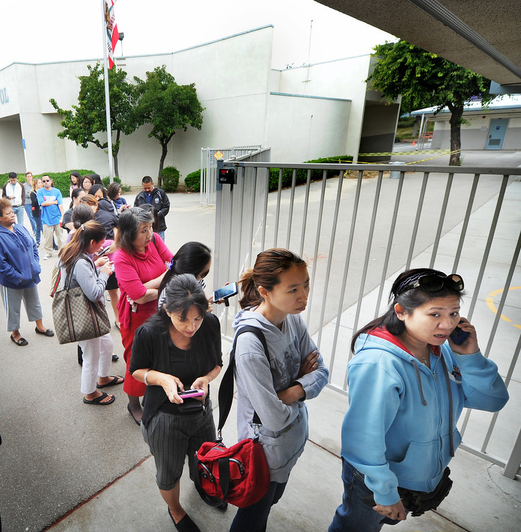 """. Concerned parents lining outside the entrance of the Brightwood School office in Monterey Park, waiting for children to be released from a lockdown at the school. A 19-year-old man was arrested for allegedly making phone calls to the California Highway Patrol threatening gun violence against local schools on Thursday, May 16, 2013. When the suspect called to make the threat, he said he was en route to a college in Monterey Park, she said. The call was made from a cell phone and was received from the East Los Angeles and Monterey Park areas, officials said.About 14 schools were locked down during the incident. At about 9:30 a.m., Santa Monica Community College police arrested a suspect, a 19-year old male in connection with this threat as well as the Santa Monica threat,\"""" Los Angeles County Sheriff\'s spokeswoman  The suspect was arrested on the Santa Monica campus and it was unclear if he had any weapons.(SGVN/Photo by Walt Mancini)"""