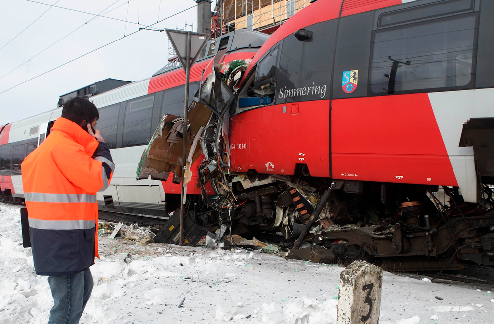 . A railway official talks on his mobile phone in front of two demolished S45 trains after a train crash in Vienna January 21, 2013. Two trains collided Monday morning, injuring 25 people, police said. REUTERS/Heinz-Peter Bader (AUSTRIA - Tags: DISASTER TRANSPORT)
