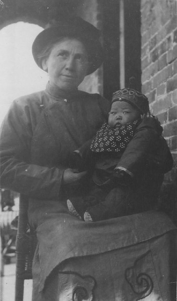 Portrait of a woman named Cameron holding a Chinese baby, ca.1900