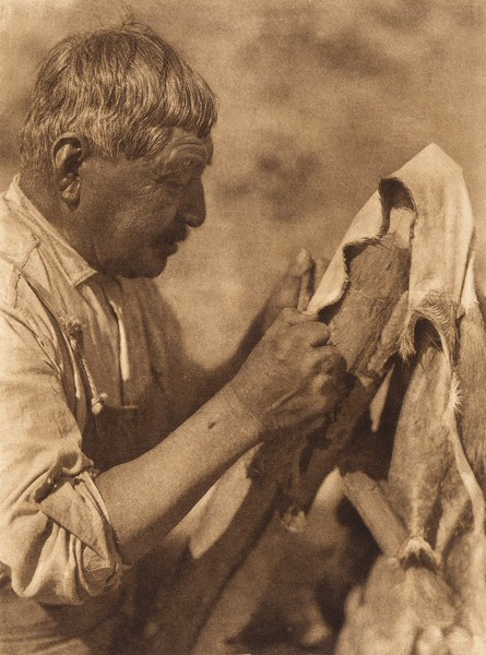 Scraping a deerskin - Washo  (The North American Indian, v. XV. Norwood, MA, The Plimpton Press, 1926)