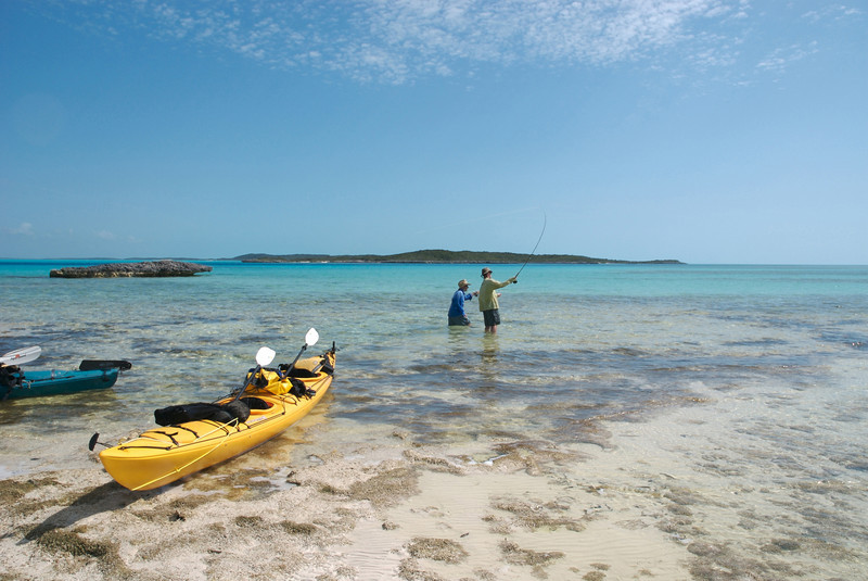 Dave Trevithick points out a large cruising Bonefish to Tim Candon on a remote kayaking trip in the Exuma Islands, Bahamas.