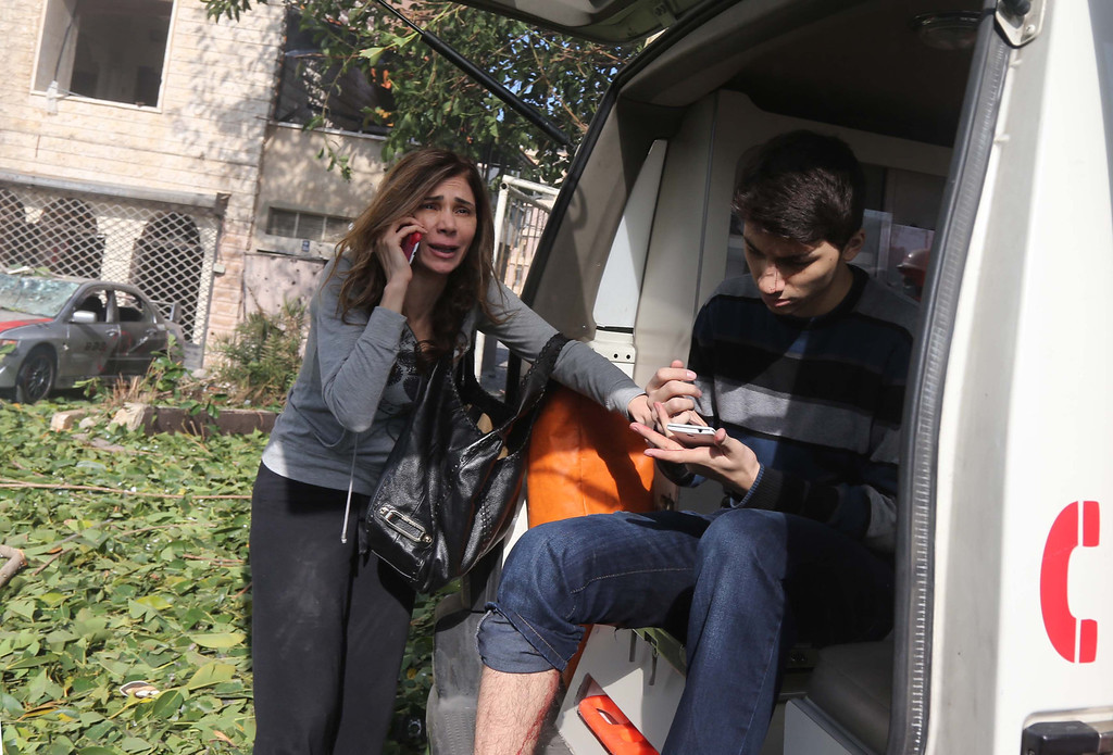 . A Lebanese woman speaks on her mobile phone next to an injured man sitting in an ambulance following a bomb explosion in a southern suburb of the capital Beirut on February 19, 2014. AFP PHOTO / STR-/AFP/Getty Images