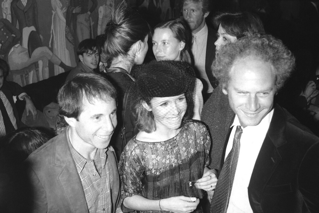 """. Carrie Fisher is flanked by her date Paul Simon, left, and Art Garfunkel, right, in New York, March 7, 1980 at a party for the cast of \""""Censored Scenes from King Kong.\"""" Party at Hisaes Restaurant marked opening of the new musical, in which Ms. Fisher stars. (AP Photo/G. Paul Burnett)"""