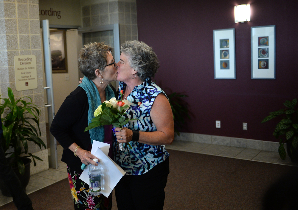 . Newlyweds Angie Holley, left, and Bylo Farmer, of Boulder, celebrate getting  their marriage license issued this morning at the Boulder County Clerk and Recorder\'s Office, June 26, 2014. Boulder County issued five more marriage licences to same-sex couples in the first hour that the Clerk and Recorder\'s Office in Boulder was open. (Photo by RJ Sangosti/The Denver Post)