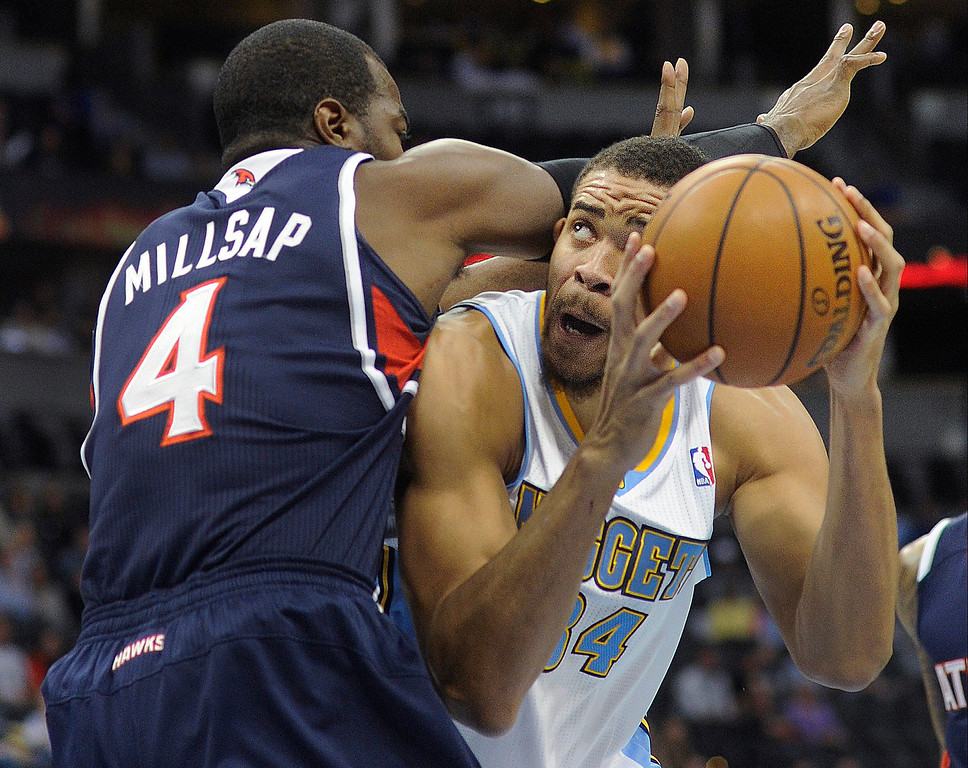 . Denver center JaVale McGee (34) got tangled up with Atlanta defender Paul Millsap (4) in the first half.  The Denver Nuggets defeated the Atlanta Hawks 109-107 at the Pepsi Center Thursday night, November 7, 2013 for its first win of the season.   Photo By Karl Gehring/The Denver Post