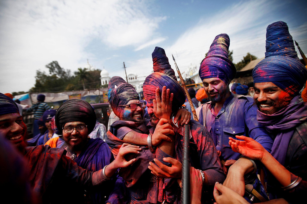 . Nihangs or Sikh warriors smear each others faces with color powder as they participate in a religious procession during the annual fair of \'Hola Mohalla\' in Anandpur Sahib, in the northern Indian state of Punjab, Monday, March 17, 2014. Believers from various parts of northern India collect at the religious fair to celebrate the festival of Holi in a tradition set by the tenth Sikh guru Guru Gobind Singh in the seventeenth century. Nihangs, or Sikh warriors, display their martial skills and attire during the fair, believed to be maintained in the exact tradition as set by the Guru. (AP Photo/Altaf Qadri)