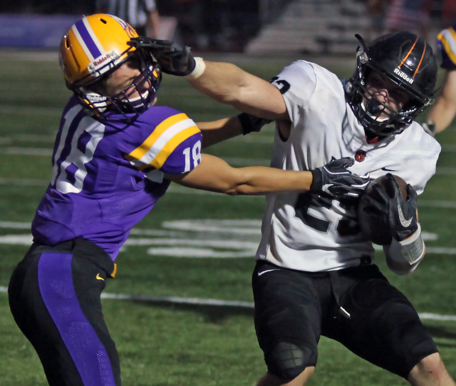 . Randy Meyers - The Morning Journal<br> North Olmsted running back Darren Anders stiff arms Niko Pappas of Avon after a short gain during the second quarter on Sept. 14.