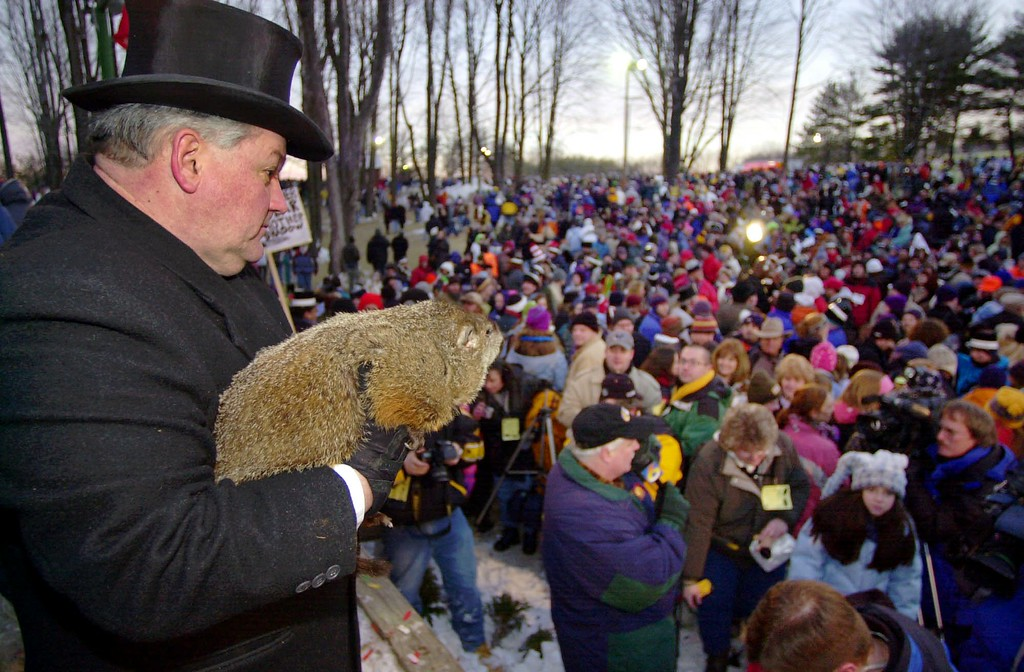 . Punxsutawney Phil, the weather prognosticating groundhog from Gobblers Knob in Punxsutawney, Pa., is held by handler Bill Deeley after seeing his shadow at 7:27 a.m., Monday, Feb. 2, 2004, and predicting six more weeks of winter. (AP Photo/Gene J. Puskar)