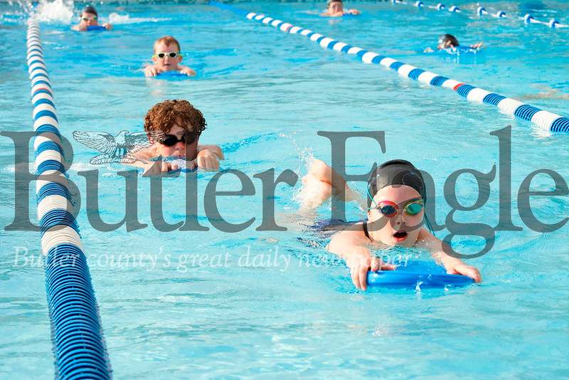 Ada Wood (front), Alex Gianakas and members of the Zelienople Area Swim Club were treated to some evening sunshine between rain showers Wednesday.  Under the guidance of their coaches, club members practiced Wednesday evening at the newly remodeled EDCO Park Pool. Seb Foltz/Butler Eagle